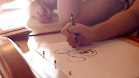 Workshop students hold pencils while drawing Mickey Mouse on special animation paper