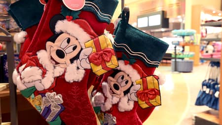 Holiday stockings featuring Mickey Mouse as Santa Claus hang from a shelf inside a theme-