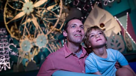 "Un padre y su hijo miran con asombro mientras navegan abordo de ""it's a small world"" en el Parque Temático Magic Kingdom"