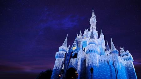 Le Cinderella Castle scintillant après la transformation Frozen Holiday Wish au parc Magic Kingdom