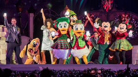 Mickey, Minnie, Donald, Daisy, Goofy, Pluto y varios actores con atuendos festivos en el escenario