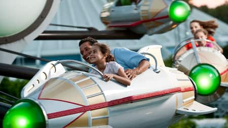 A father and daughter hold tightly to one another as they ride aboard Astro Orbiter in Tomorrowland