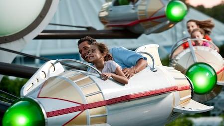 Un père et sa fille se tiennent fermement à bord du manège Astro Orbiter à Tomorrowland