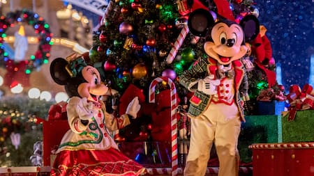 Mickey and Minnie Mouse dressed in festive holiday clothing while standing next to a Christmas tree