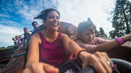 Una madre y su hija disfrutando de un paseo a bordo de Seven Dwarfs Mine Train en Fantasyland