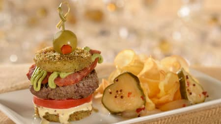 A slider composed of fried zucchini, tomatoes, ham, beef patty, sauce and an olive near pickles and potato chips