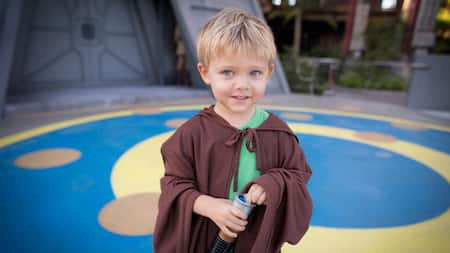 A young Guest dressed as a Jedi Knight holding a lightsaber by Star Tours – The Adventures Continue