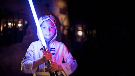 A child dressed as R2D2 holds a glowing lightsaber
