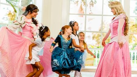 Cuatro niñas pequeñas practican sus reverencias con las Princesas Aurora y Miss Rose Petal en Disney's Perfectly Princess Tea