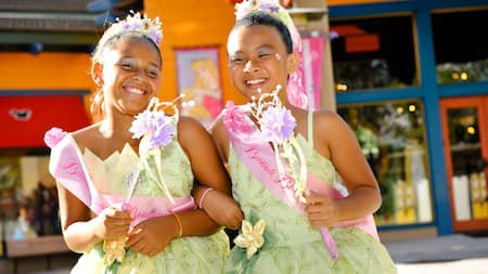 Two girls holding flower wands pose arm and arm in matching Princess Tiana dresses, tiaras and sashes reading Bibbidi Bobbidi Boutique