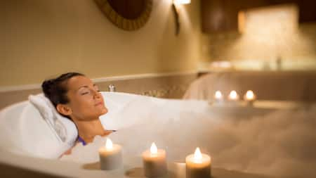 Una mujer con los ojos cerrados se relaja recostada en un baño de burbujas