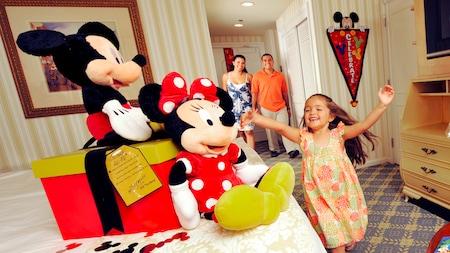 Una niña pequeña y sus padres que recién entraron a una habitación de hotel se emocionan al descubrir muñecos de peluche de Mickey y Minnie Mouse y una caja de regalos sobre la cama