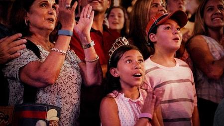 Varias personas miran hacia arriba y aplauden maravillados