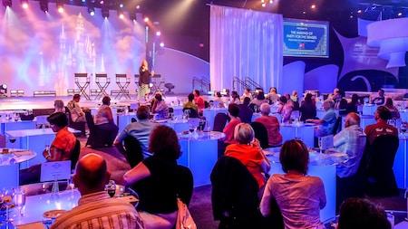 """Una mujer habla en un escenario a un público sentado en mesas con vasos de vino y pequeños platos de comida. Sobre el escenario, aparece un cartel que dice """"The Making of Party for the Senses, from Idea to Implementation"""" (La preparación de una fiesta para los sentidos: de la idea a la implementación)"""