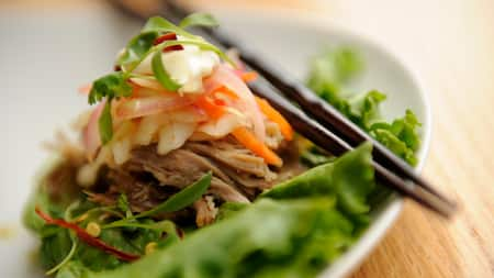 An Asian dish comprised of a lettuce leaf topped with shredded meat, pickled onion and a sauce