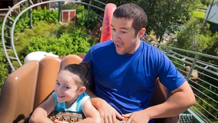 A dad and daughter smile excitedly while riding The Barnstormer roller coaster at Magic Kingdom park