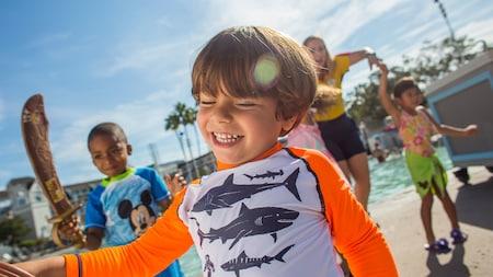 Un groupe de jeunes visiteurs en maillots de bain dansent avec un membre de l'équipe lors d'une fête Disney Junior au bord de la piscine
