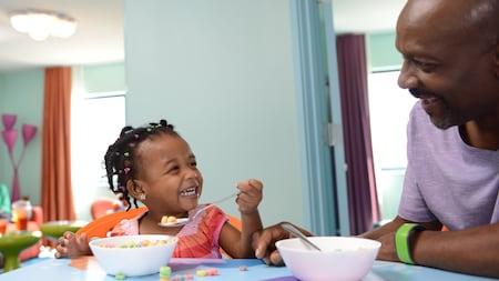Pai e filha rindo juntos saboreiam um café da manhã com cereal em um hotel Resort Disney