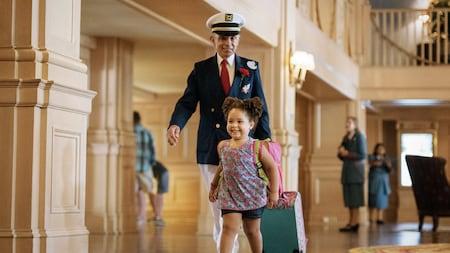Uma menina sorri alegremente enquanto um funcionário da Disney idoso segura a sacola dela no Disney's Yacht Club Resort