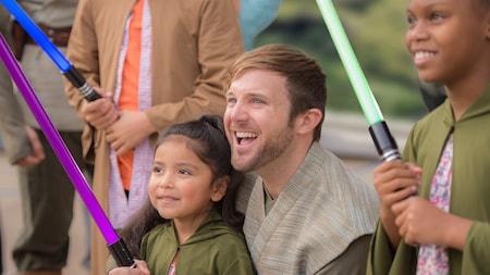 Un Jedi acompaña a una niña pequeña que sostiene un sable de luz de juguete