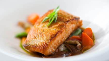 Roasted salmon sitting on a bed of cooked vegetables