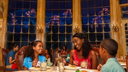 Uma família sorri, sentada a uma mesa de um restaurante agitado
