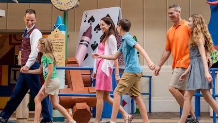 Una familia emocionada sonríe mientras sigue a un entusiasta guía de excursiones VIP hacia Toy Story Midway Mania