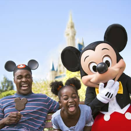 A man and a little girl laugh next to Mickey Mouse in front of Cinderella Castle