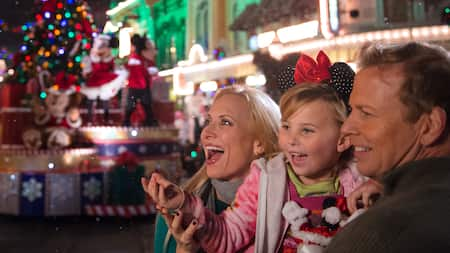 A family smiling while watching a holiday parade