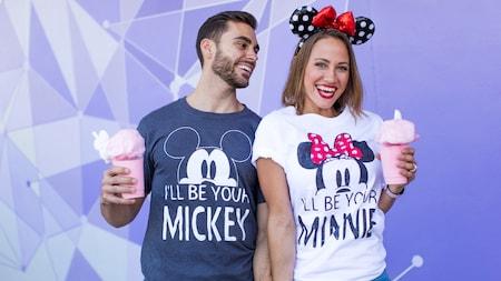 Um casal alegre usando camisetas combinando do Mickey e da Minnie e sorrindo em uma pose com um doce gelado
