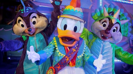 Chip and Dale dressed up as dinosaurs stand next to Donald Duck dressed in a safari outfit