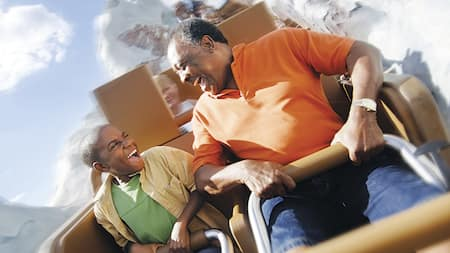 A boy and his grandfather sharing a laugh aboard a rollercoaster rushing through scenery resembling a snow capped mountain