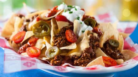 Un plato de nachos cubiertos con chiles, jalapeños, tomates, sour cream y cebollines
