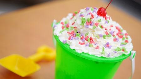 Un balde de helado cubierto con crema batida, chispas arcoíris y una cereza