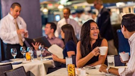 Visitantes piden comida y beben café en el restaurante Flying Fish