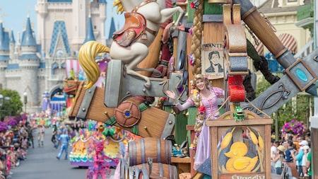 Un desfile frente a Cinderella Castle, con Rapunzel sobre una carroza en forma de barco y más Personajes detrás de ella