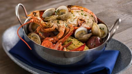 A metal pot filled with clams, corn and half a lobster