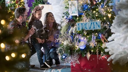 A family looks at a decorated Christmas tree with an ornamental sign that reads Frozen