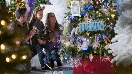 Una familia mira un árbol de Navidad decorado con un cartel decorativo que dice Frozen