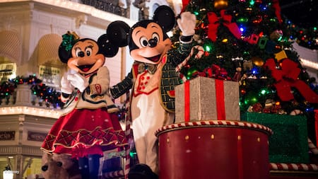 d9241ff329ccb Dressed in holiday attire, Mickey Mouse and Minnie Mouse wave from in front  of a