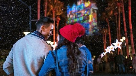 A couple looks at palm trees and a building covered in festive lights