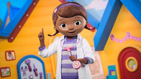Doc McStuffins, holding her stethoscope and gesturing in front of her office