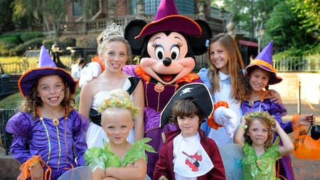 Dressed as a friendly witch, Minnie Mouse stands with 7 children who are also in Halloween costumes