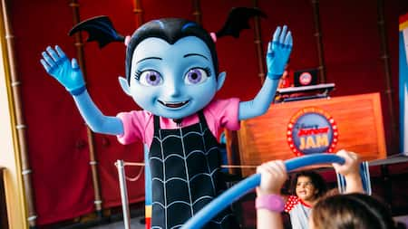 Vampirina stands with her arms raised near a sign that reads 'Disney Junior Jam'