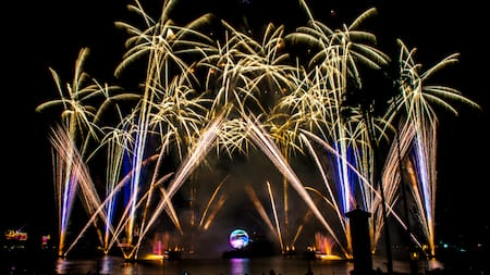 A burst of fireworks over a colorful array of light beams emanating from a lake