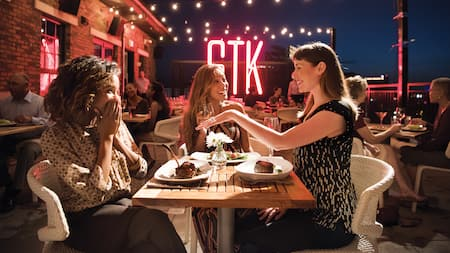 3 women share a laugh over dinner at STK Steakhouse
