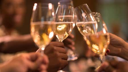 Several hands bring glasses of white wine together in a toast