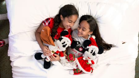 2 young siblings snuggle together, holding their Mickey Mouse and Minnie Mouse plush toys