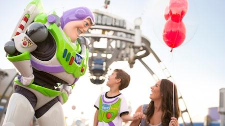 Una mujer y un niño le sonríen a Buzz Lightyear