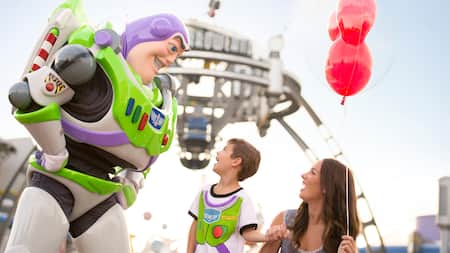 A woman and a boy smile at Buzz Lightyear